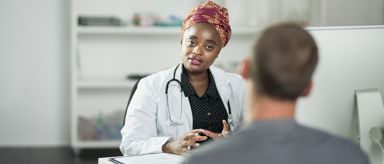 primary care physician listens to low-income patient