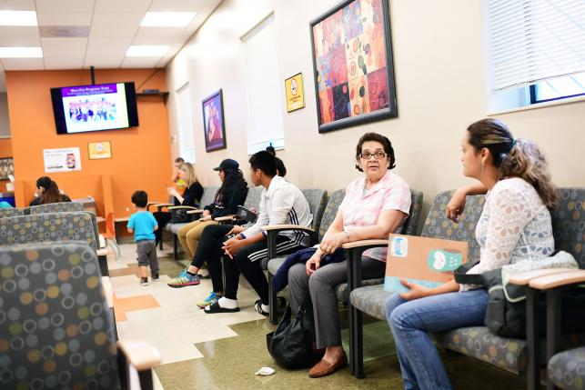 Patients sitting in a free health clinic waiting room.