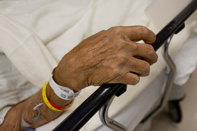 An elderly patient admitted to the emergency room waits to be seen by a doctor.