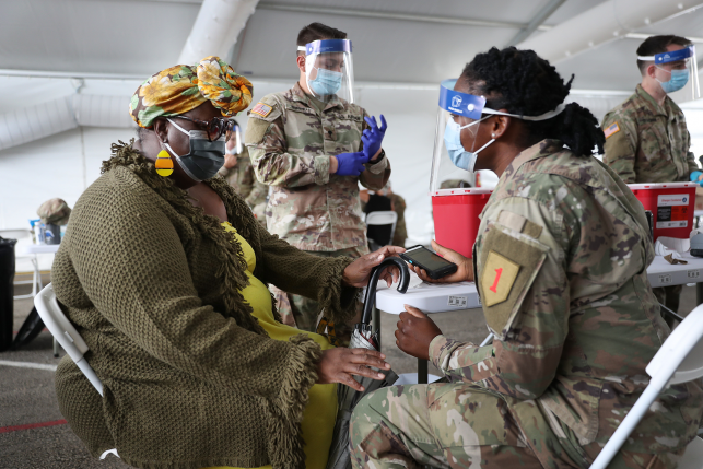 A U.S. Army soldier from the 2nd Armored Brigade Combat Team, 1st Infantry Division, prepares to immunize Tangela C. Mitchill with the COVID-19 vaccine at the Miami Dade College North Campus on March 10, 2021 in North Miami, Florida.