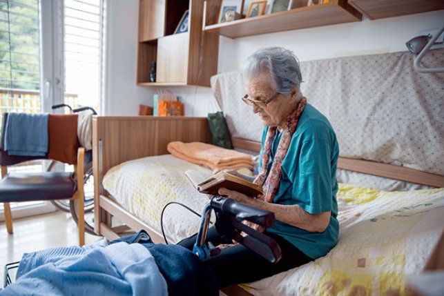 Medicare senior who is seriously ill reading on bed