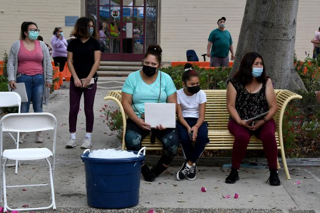 Masked people sitting on a bench after getting flu shots at a walk-up health clinic