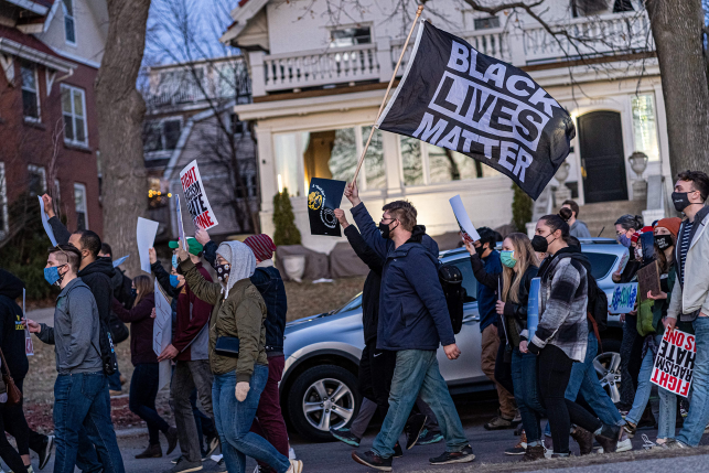 "A man waves a Black Lives Matter flag as people march during the ""Asian Solidarity March"" rally against anti-Asian hate in response to recent anti-Asian crime on March 18, 2021, in Minneapolis."