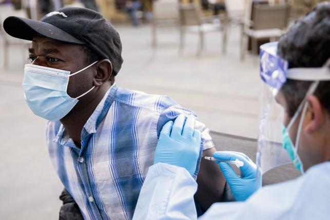 Black American wearing a surgical mask recieves a vaccine dose
