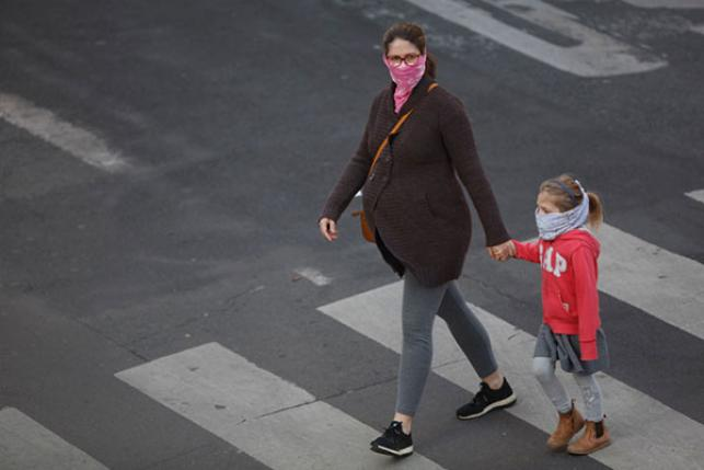 pregnant woman walking with child and masks during COVID-19 outbreak