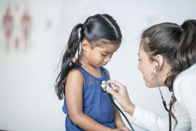 Immigrant child receiving medical treatment from a doctor