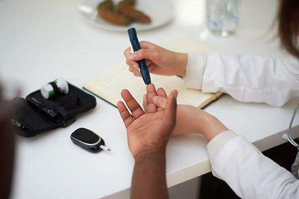 doctor testing blood of diabetes patient
