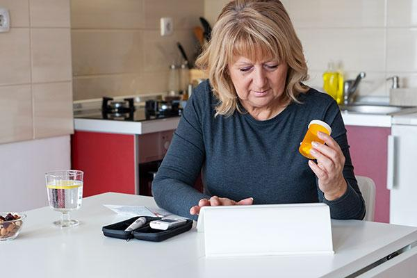 woman doing telehealth while checking blood sugar at home