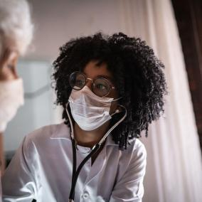 Doctor wearing a surgical mask speaks to a patient