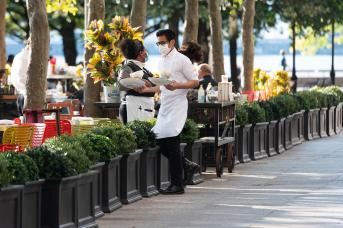 A waiter wears a face mask while carrying food outside P.J. Clarke's at Brookfield Place on September 30, 2020 in New York City.