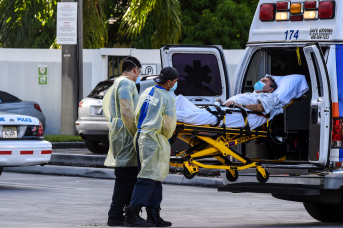 Medics transfer a patient on a stretcher from an ambulance outside of Emergency at Coral Gables Hospital where Coronavirus patients are treated near Miami, Florida.