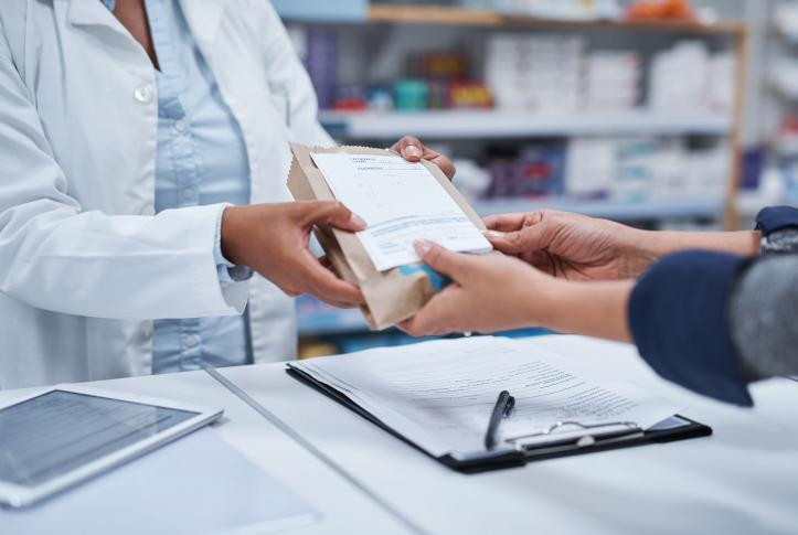 Pharmacist handing a customer a prescription package.