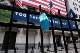 Health Care in 2020 Year in Review face mask hanging in front of the New York Stock Exchange