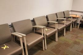 Chairs blocked off in an empty doctor's office waiting room