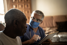 Health visitor and a senior man during home visit