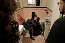Doulas demonstrating how a birthing person can be supported while in hte bathroom